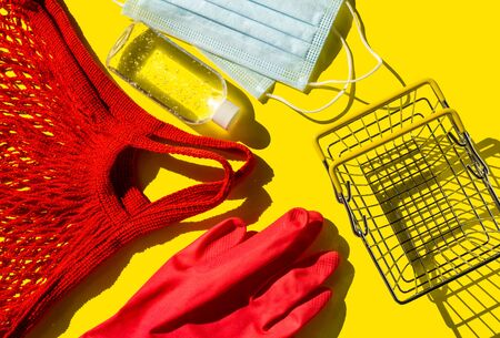 Reusable red shopping bag-a string bag, disposable glove, sanitizer and metal shopping basket. Necessary kit for visiting the store during the coronavirus pandemic. Zero waste vs plastic. Top view. Imagens