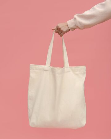 A woman's hand holds a trendy bag on a pink background. The concept of zero waste. Reusable light cotton shopper bag for going to the supermarket instead of plastic bags. Imagens