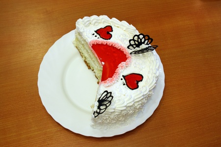fancy sweet box: white cake decorated with red hearts on a red background on a white plate cutted