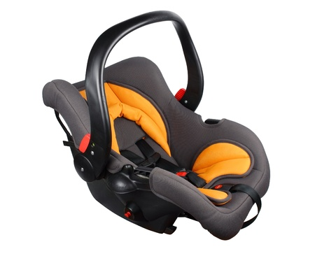 Baby black and orange car seat isolated against a white background photo