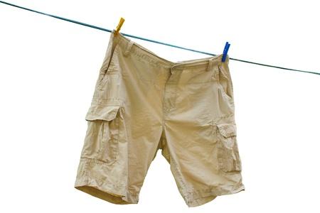 impiccata: Pantaloncini beige carico impiccati a clothespegs Archivio Fotografico