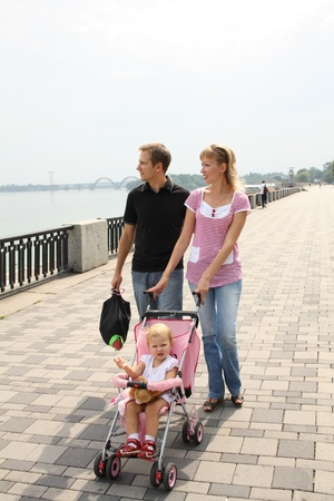 family walking on embankment looking at the river photo