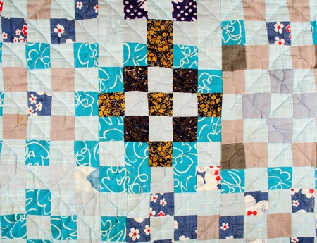 patchwork quilt background with different colors mostly blue photo
