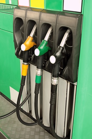 Gas nozzles at the gas station A row of 3 different gas pumps black yellow and green photo
