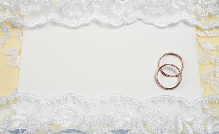 wedding invitation decorated with lace with rings over it photo