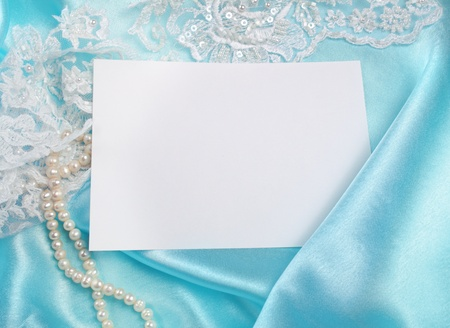 wedding invitation over blue silk and lace