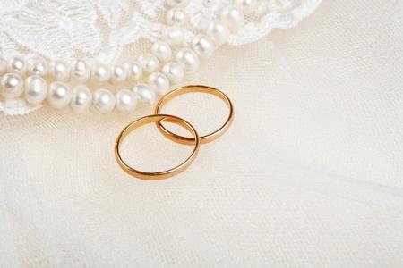 Paar gouden trouwringen op uitnodigingskaart versierd met kant