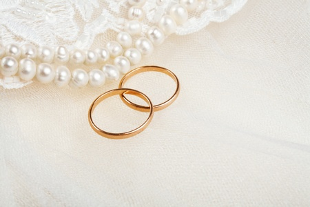 Pair of golden wedding rings over invitation card decorated with lace Stock fotó
