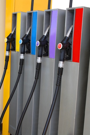 Gas nozzles at the gas station A row of 4 different gas pumps yellow, blue, purple and red Stock Photo - 10795707