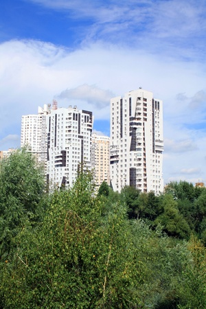 multistoried apartment building with trees against blue sky and white clouds photo