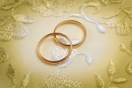 Pair of golden wedding rings over invitation card decorated with lace photo
