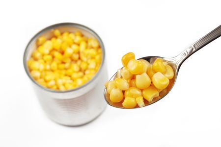opened corn can with spoon filled with cond, isolated on a white background Banco de Imagens