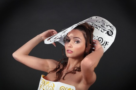 Gorgeous glamour woman close up in big white paper hat isolated over black background Stock Photo - 13013427