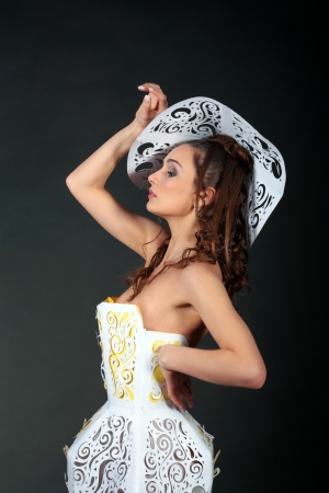 fashion girl in paper dress and hat over black background photo
