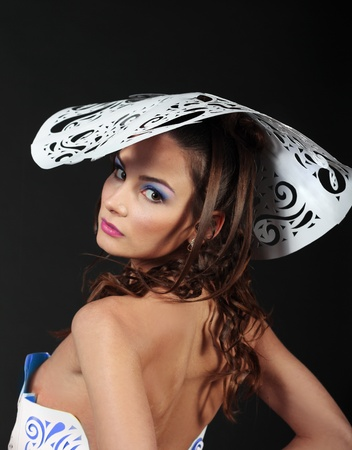 Gorgeous glamour woman close up in big white paper hat isolated over black background photo