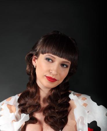 trenzas en el cabello: Atractiva mujer morena con labios rojos y pelo trenzado sobre backgound gris oscuro