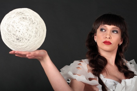 Attractive brunette woman in paper dress holding white light ball in her hands illuminated Stock Photo - 13401364