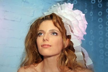 Beautiful Fashion Young Woman in Paper headdress, Red Hair.  Blue background with copy-space photo