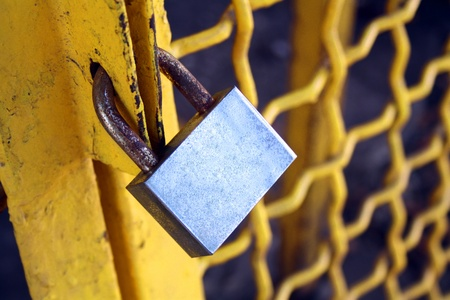 brass padlock and chain on yellow cell door photo