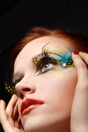 eyeshades: Gorgeous Young model beautiful women with perfect art make up, red lips and long false eyelashes made from feathers Stock Photo