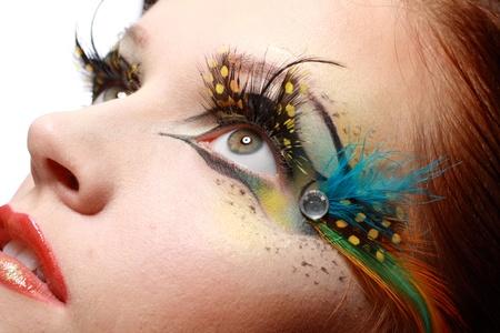 pesta�as postizas: Preciosa modelo de la mujer hermosa joven con el arte perfecto maquillaje y largas pesta�as falsas hechas de plumas Foto de archivo
