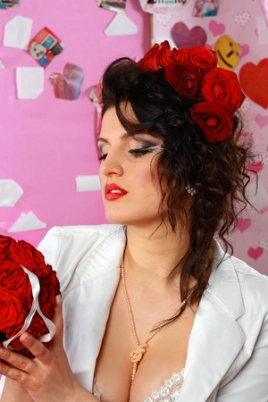 Fashion shoot of attractive brunette woman with red roses in hair photo