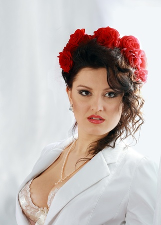 Fashion shoot of attractive brunette woman with red roses in hair white jaket photo