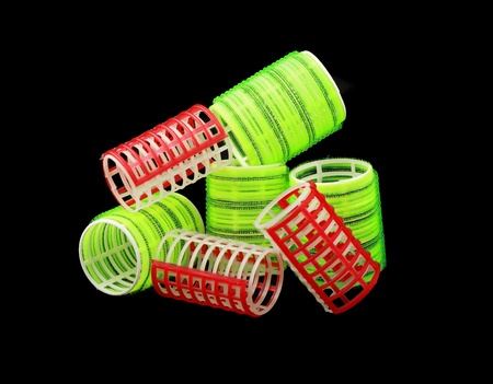 hair roller: red and yellow green curlers isolated on black background