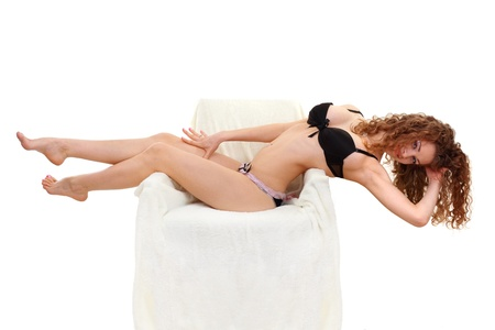 portrait of beautiful sexy young women in underwear lying on furry white armchair isolated on white background photo