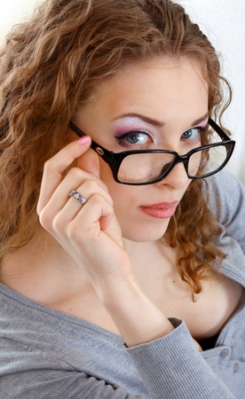 beautiful young woman face with perfect make up looking over glasses photo