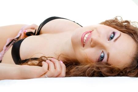 one sheet: Bella ragazza vicino di posa e di relax nel letto sorridente alla fotocamera