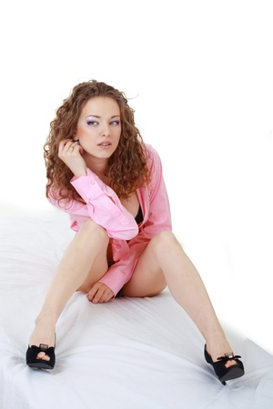 Beautiful woman in pink shirt and black shouse sitting on the bed white background photo