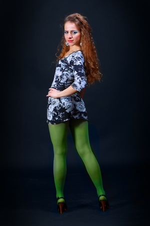 Young pretty woman in jersie dress and green tights photo