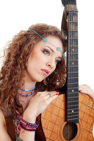 Beautiful woman holding her old guitar in hippie outfit on white background isolated photo
