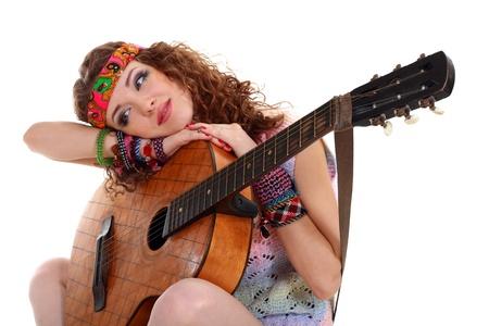Mooi Meisje met gitaar spelen op een witte achtergrond in hippie outfit geïsoleerd