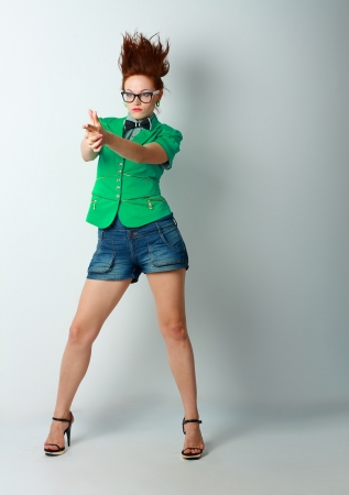 Portrait of young woman with  with finger guns shooting with hair stand on end photo