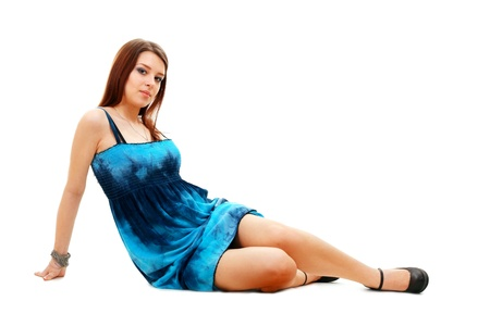 Beautiful woman sitting on the floor wearing a dress - isolated
