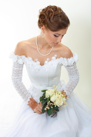 Beautiful young woman in white dress and pearl necklace beige background with henna tatoo applyed to her hands and with wedding bouquet Stock fotó