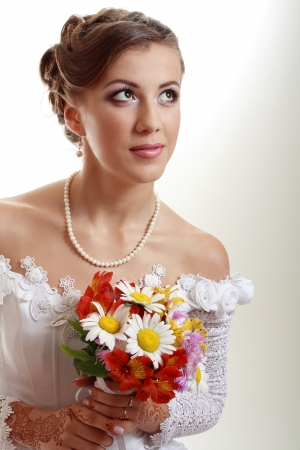 Beautiful young woman in white dress and pearl necklace beige background with henna tatoo applyed to her hands and with wedding bouquet Stock Photo - 13876539