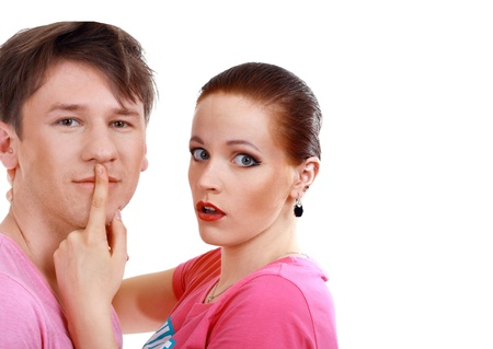 woman shuts man's mouth by index finger isolated on white background photo