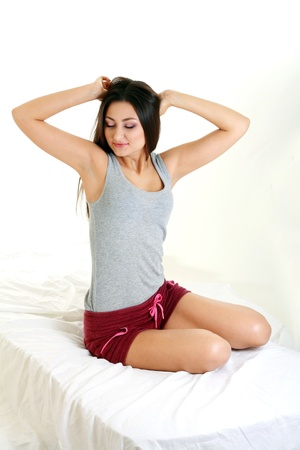 stratching: young beautiful brunnete woman just awake stratching sitting on the bed Stock Photo