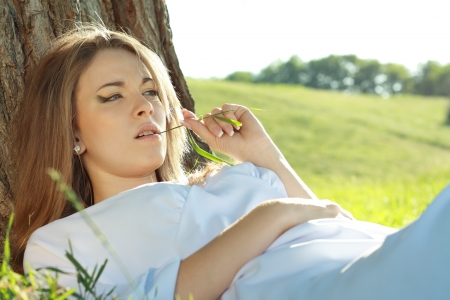 beautiful woman close up laying under the tree outdoor with field on the background with room for text. Soft summer colors photo