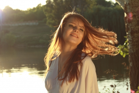 Closeup of a smiling young woman with fly hair over bright background outdoor shiny hair. Soft summer colors photo