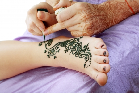 Image detail of henna being applied to leg Stock Photo