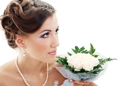 portrait of a beautiful bride looking to a bouquet of flowers photo
