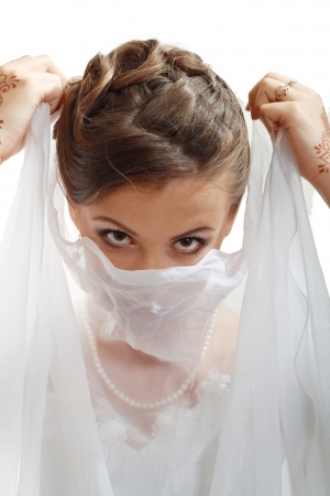 Young brunette beauty or bride, behind a white veil photo