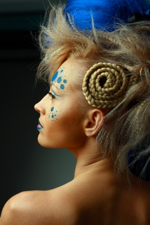 beautiful fashionable young woman with creative hairstyle with blue hairs and art make up photo