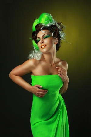 beautiful fashionable smiling young woman with creative hairstyle with green false hairs and art make up photo