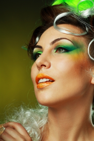beautiful fashionable young woman with creative hairstyle with green false hairs and art make up close up photo