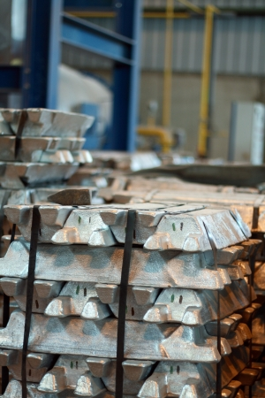 Stack of raw aluminum or steel ingots in factory. Industrial plant photo